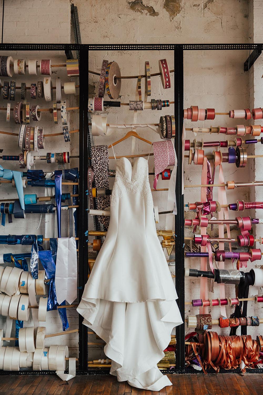 wedding dress hanging in an art factory wedding venue ribbon wall
