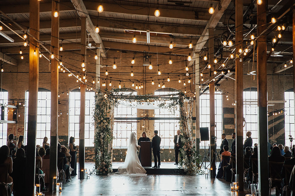 industrial string lights and greenery for an art factory wedding venue ceremony