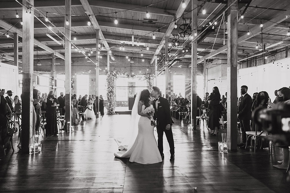 bride and groom kissing during their recessional in an art factory wedding venue