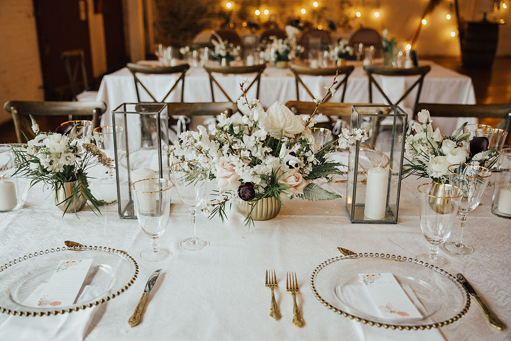 neutral centerpieces in gold vessels at an art factory wedding venue reception