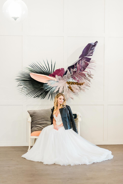 black leather bridal jacket and tropical leaf chandelier wedding decor