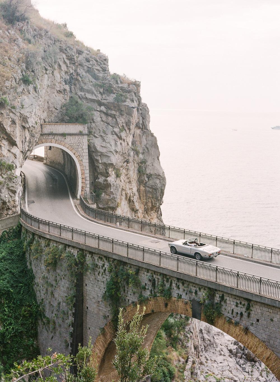 cruising along the Amalfi Coast in a vintage car