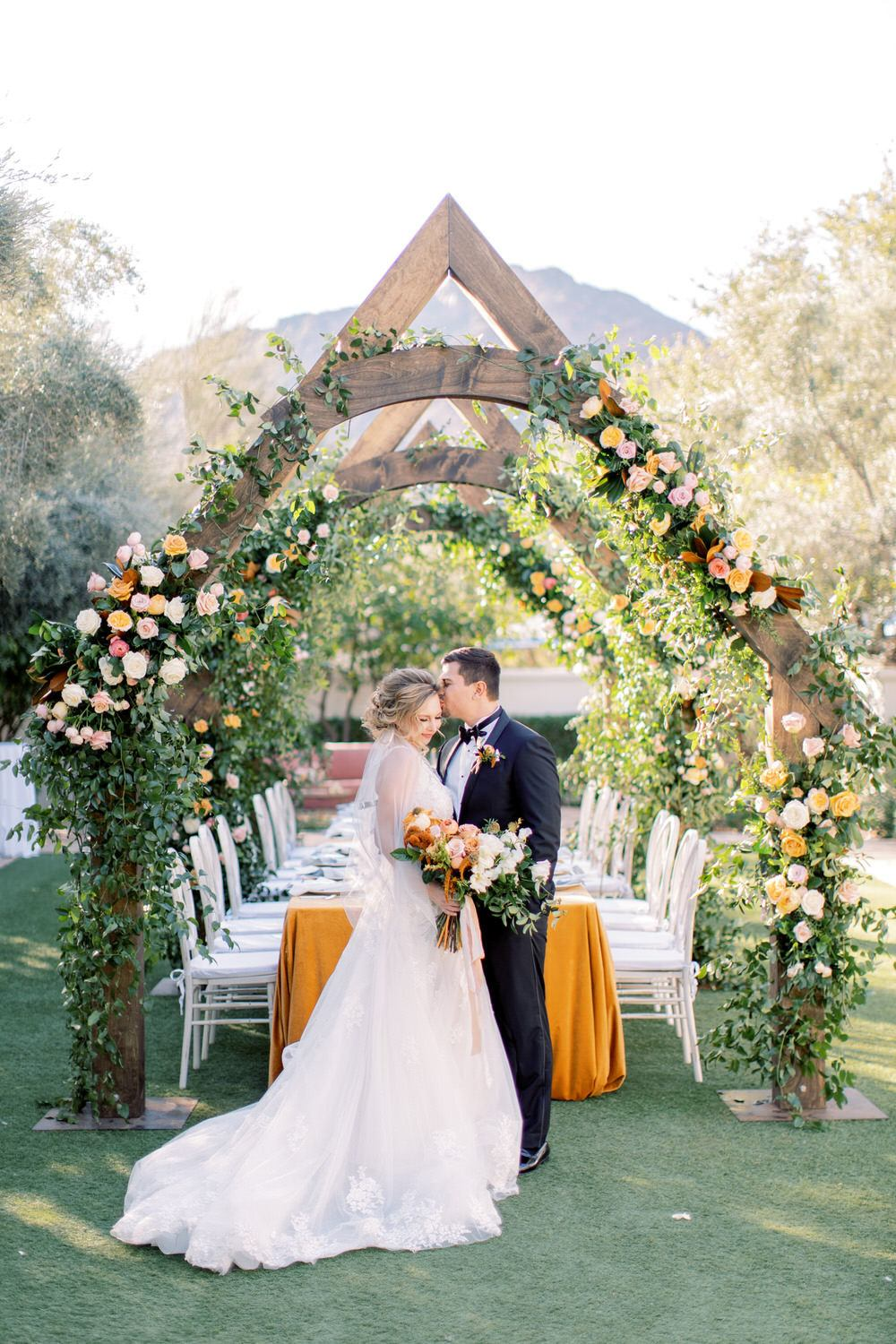 wooden arches decorated in lush florals with the groom kissing the bride's head underneath it all