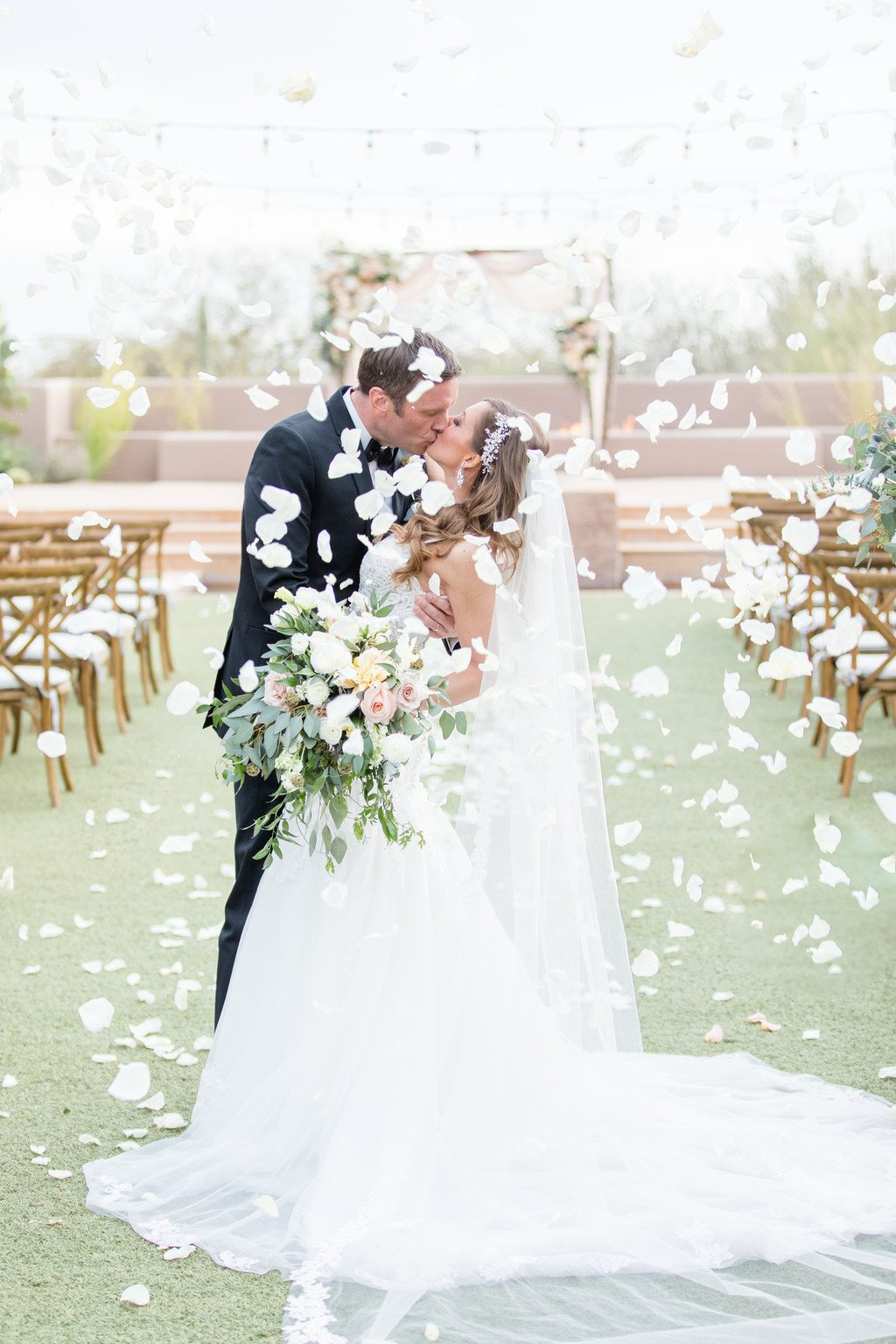 bride and groom kiss and flower petals fall around them