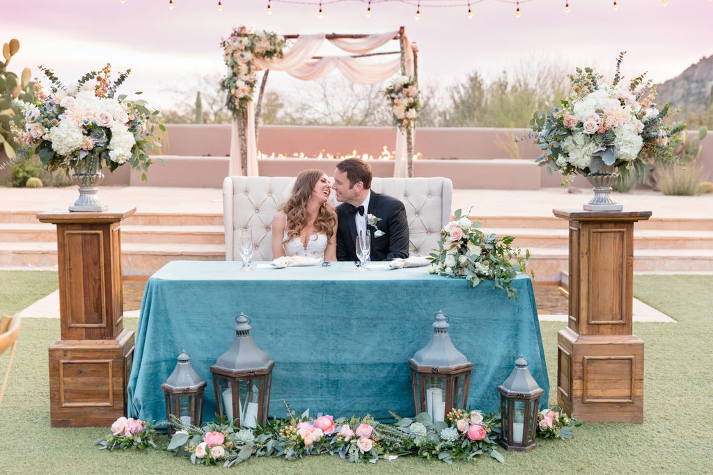 bride and groom sitting on beautiful love seat during reception
