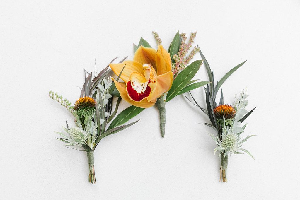 tropical orange boutonnieres - https://ruffledblog.com/vibrant-atlanta-wedding-inspiration-with-rust-accents