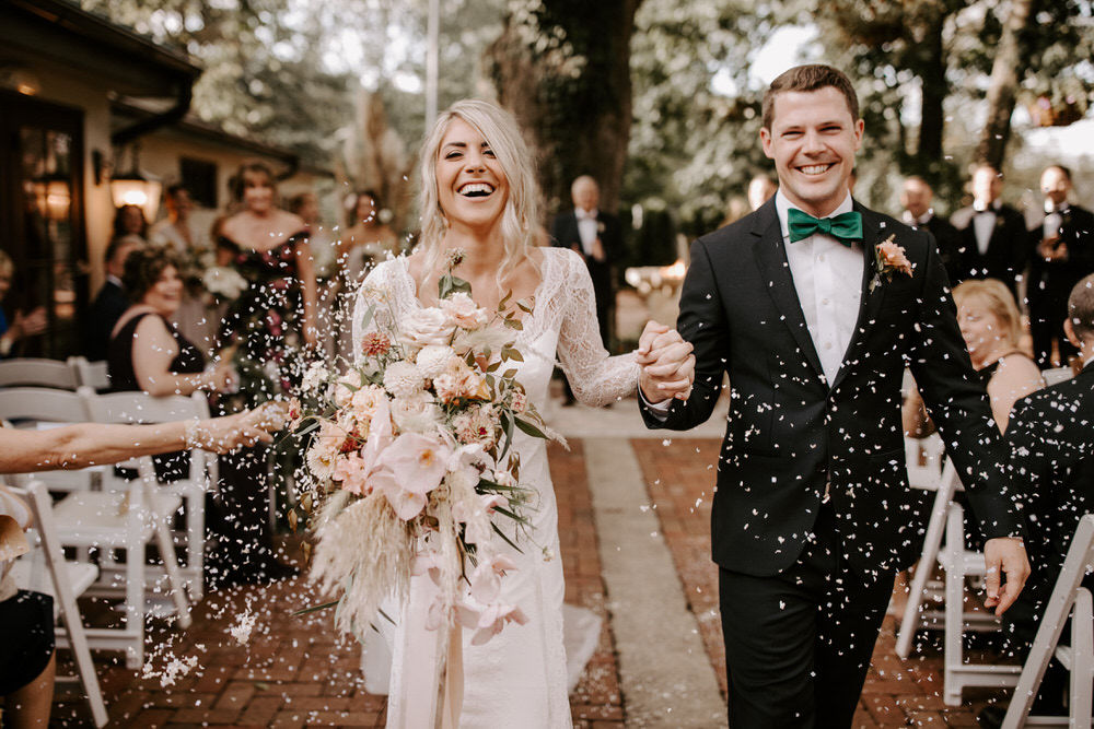 bride and groom laugh as guests throw confetti