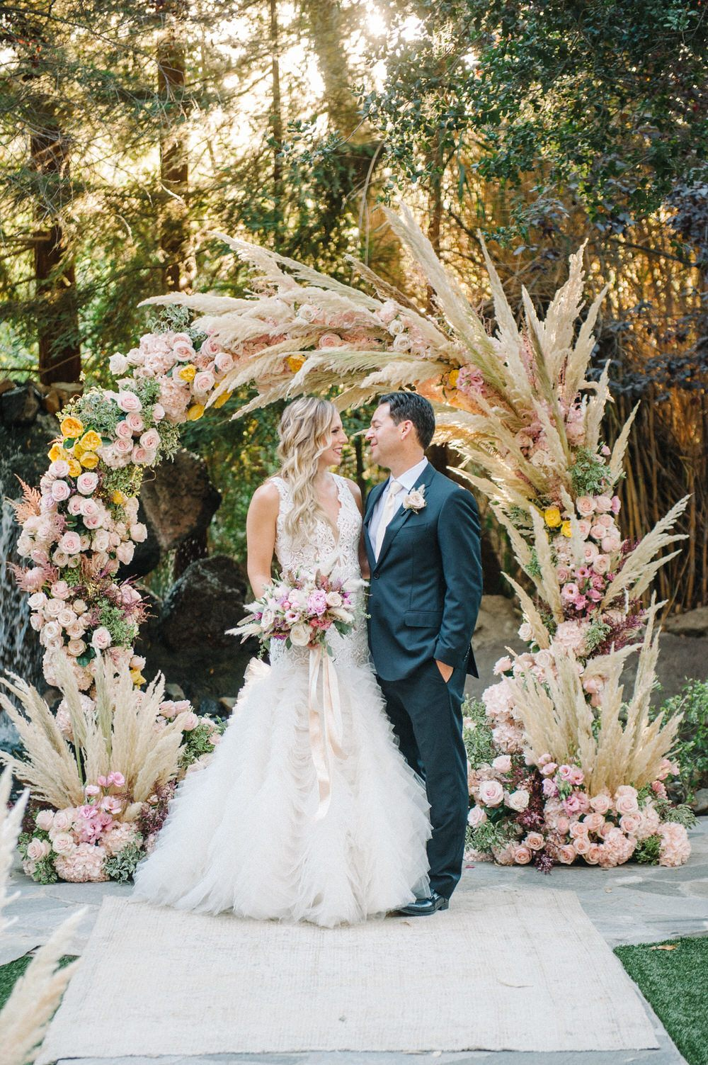 bride and groom smile in front of pampas grass ceremony decor