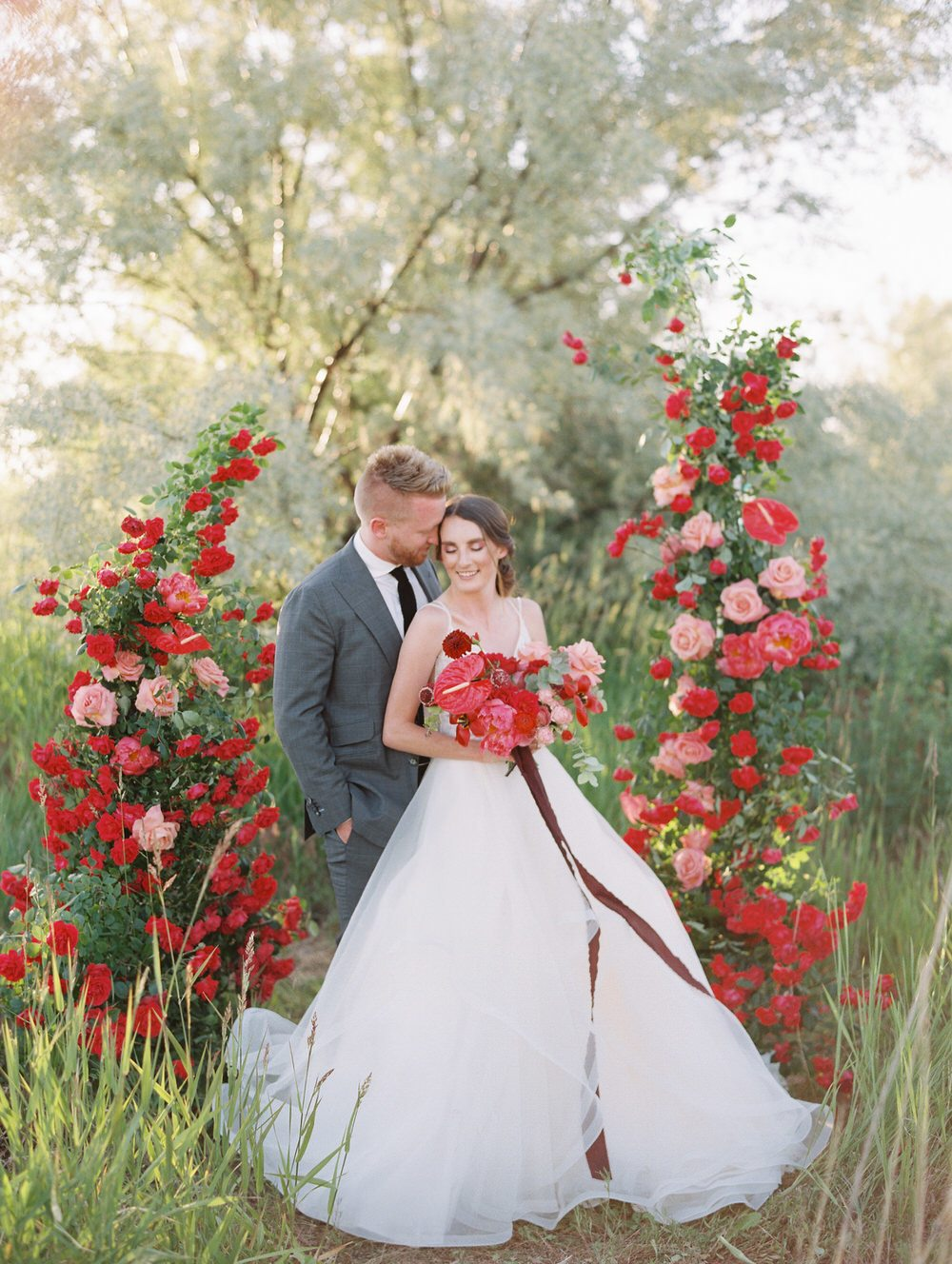 bride and groom surrounded by red roses