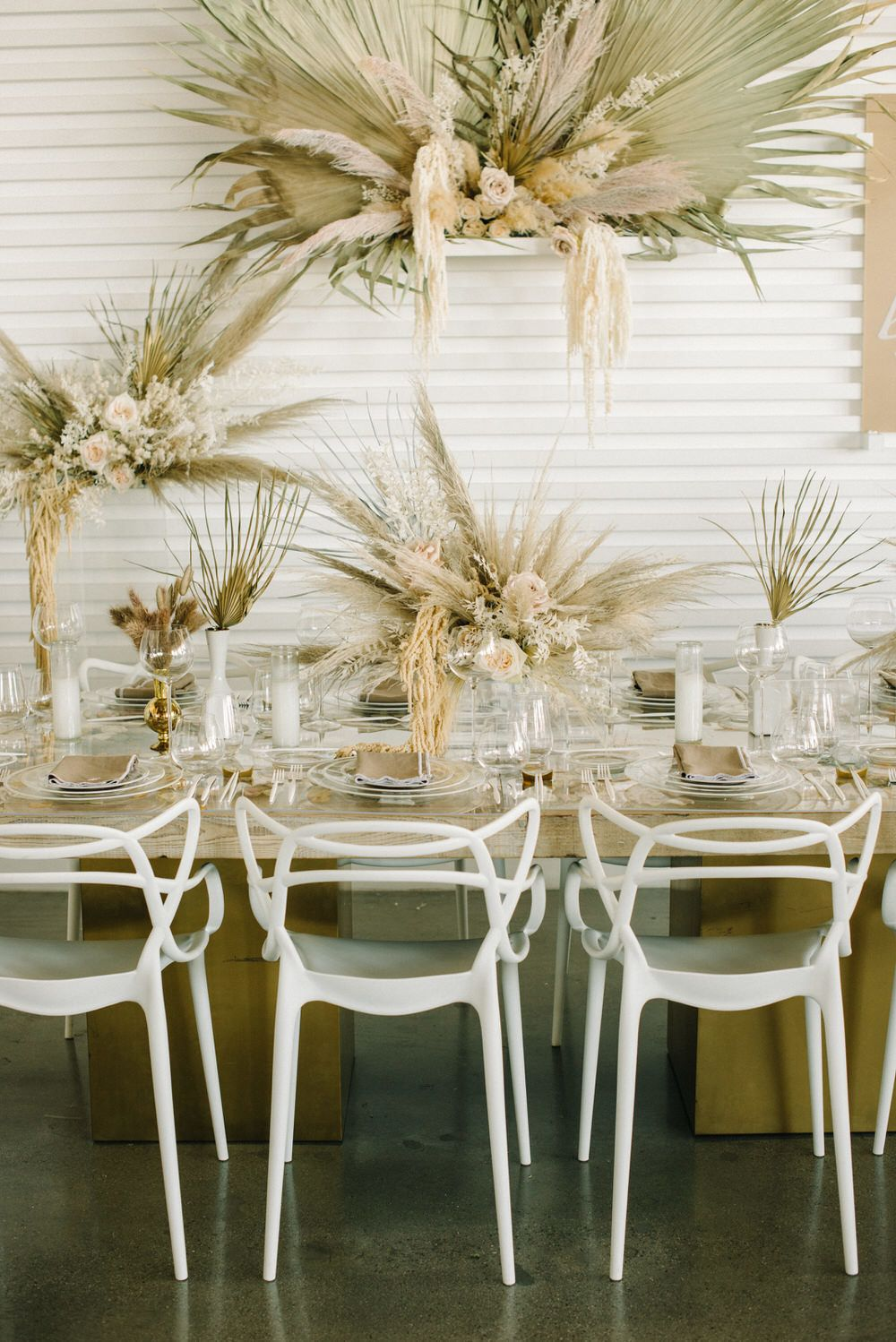 white chairs and pampas grass wedding reception decor