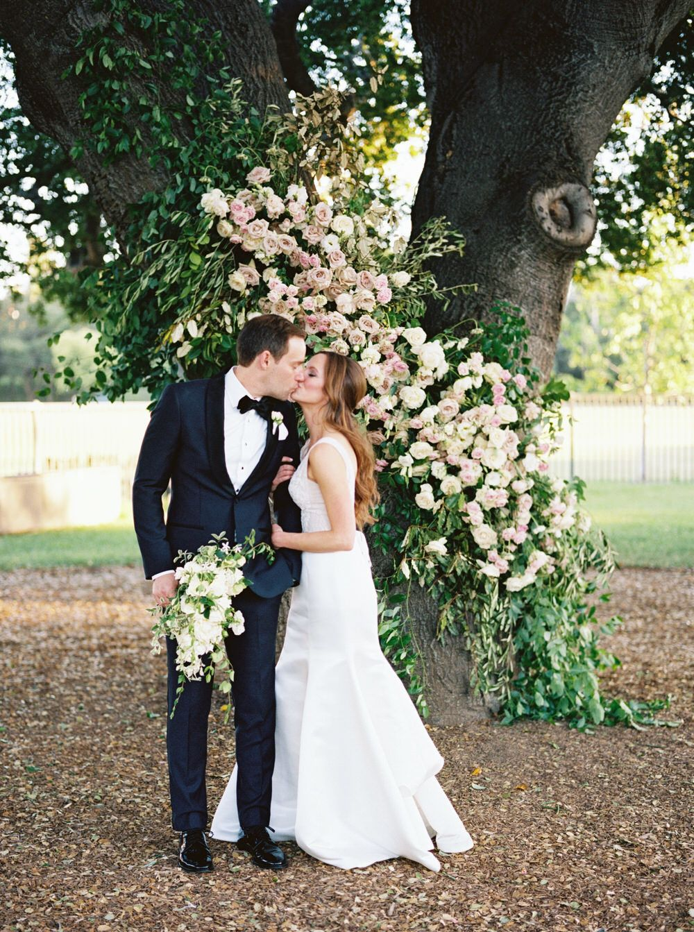 bride and groom kiss under a tree with a lush floral installation