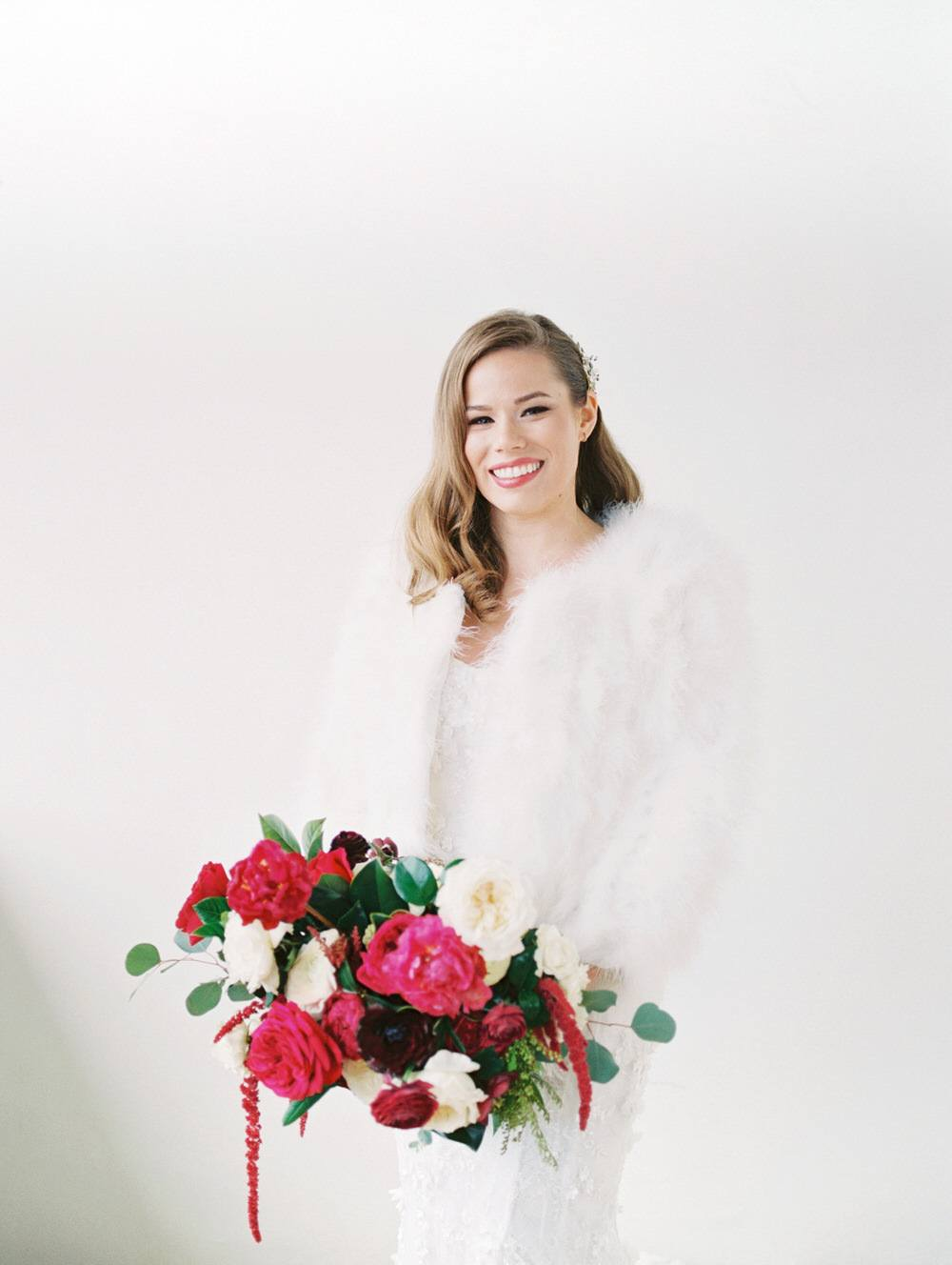 bride wearing a fluffy white shawl while holding her colorful bouquet