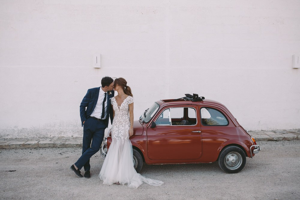 bride and groom kiss outside of their red getaway car