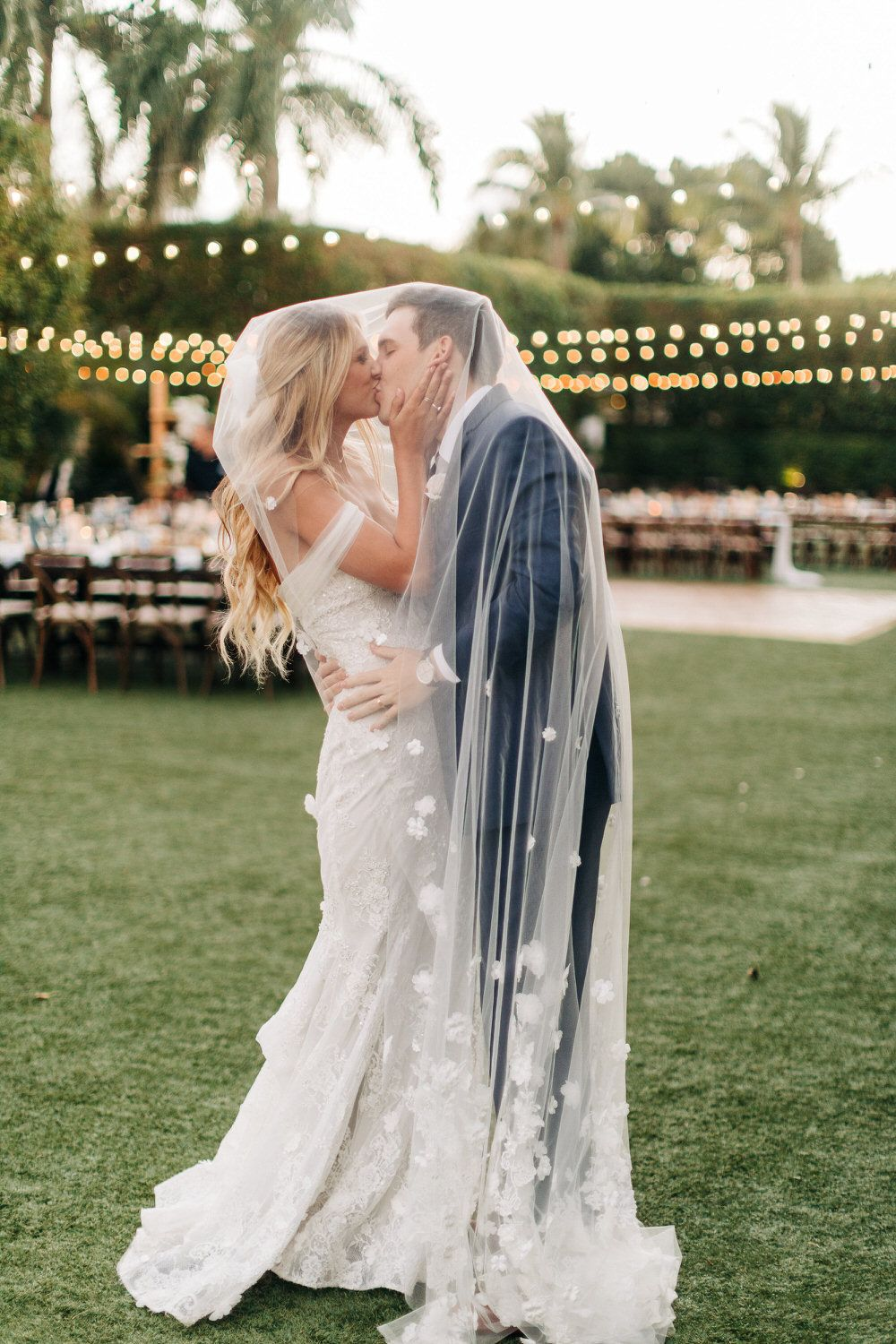 bride and groom kiss under the bride's veil