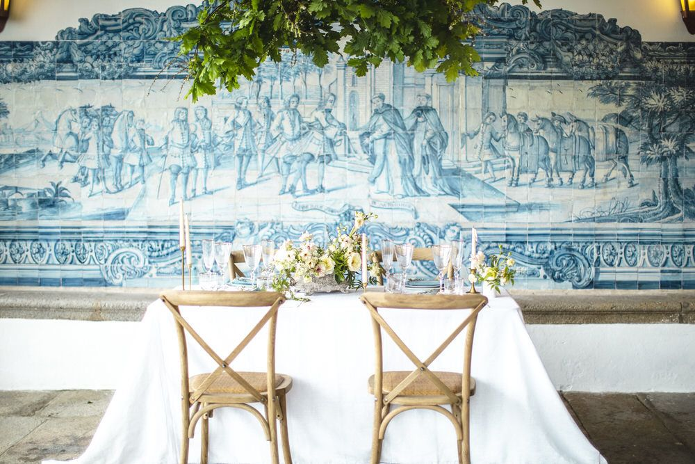 blue and white tiled backdrop with hanging lush greenery over the reception table