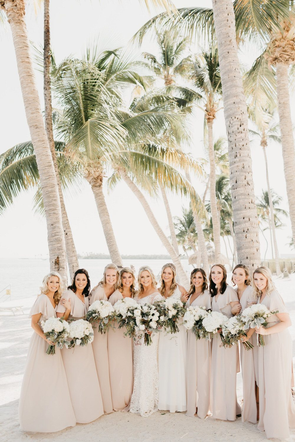 bride with her bridesmaids in floor length flowy dresses