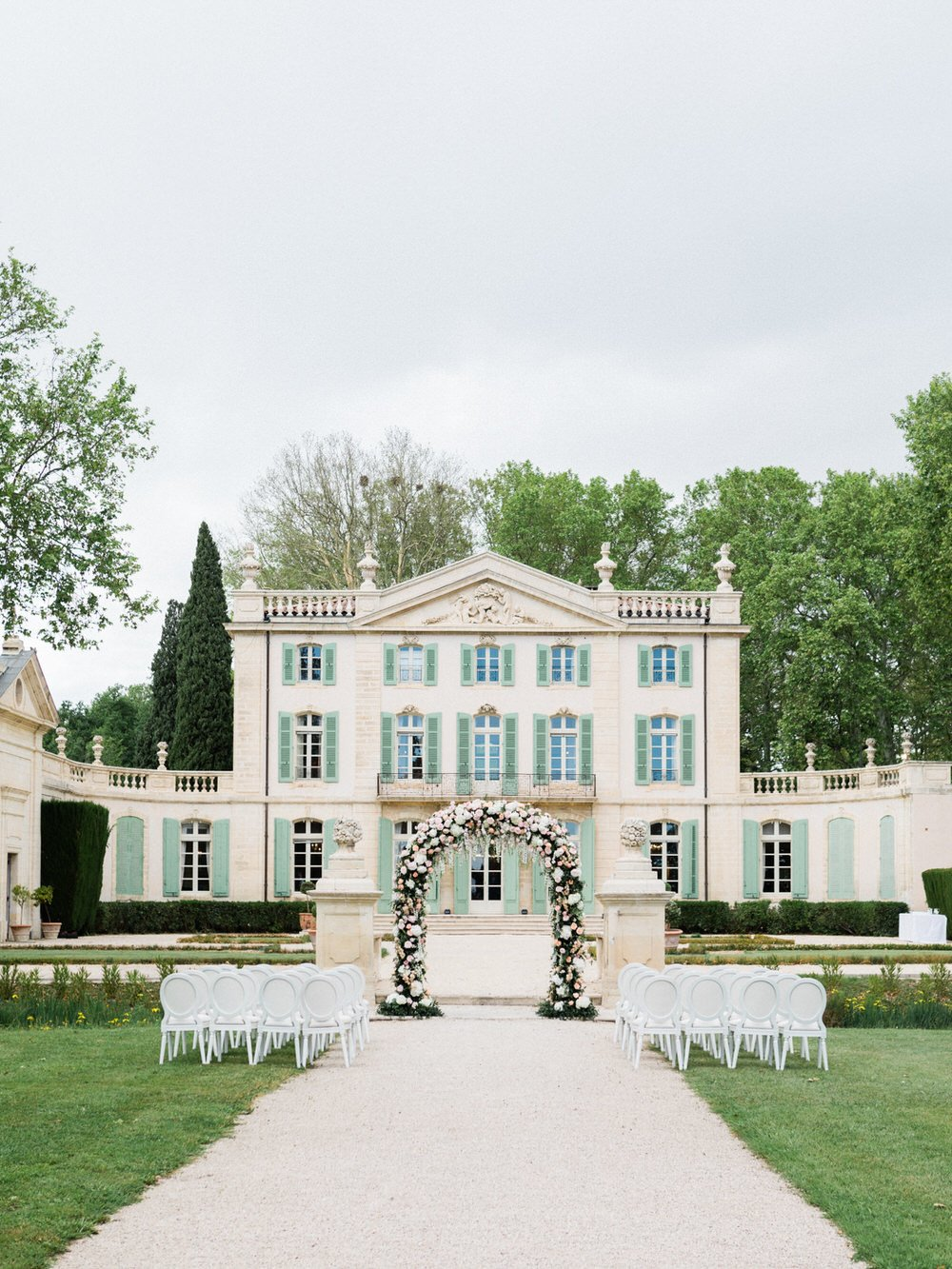 french chateau wedding ceremony with a floral arch
