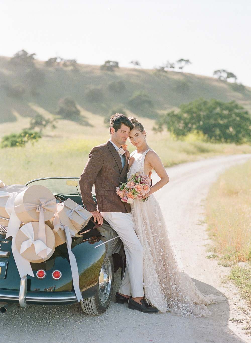 bride and groom standing next to their getaway car