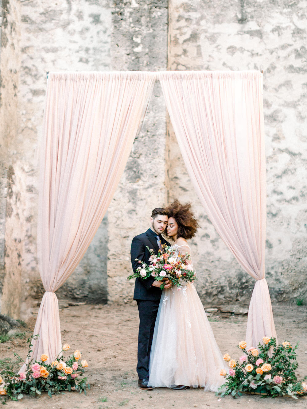 soft blush pink draping at wedding ceremony with bride and groom