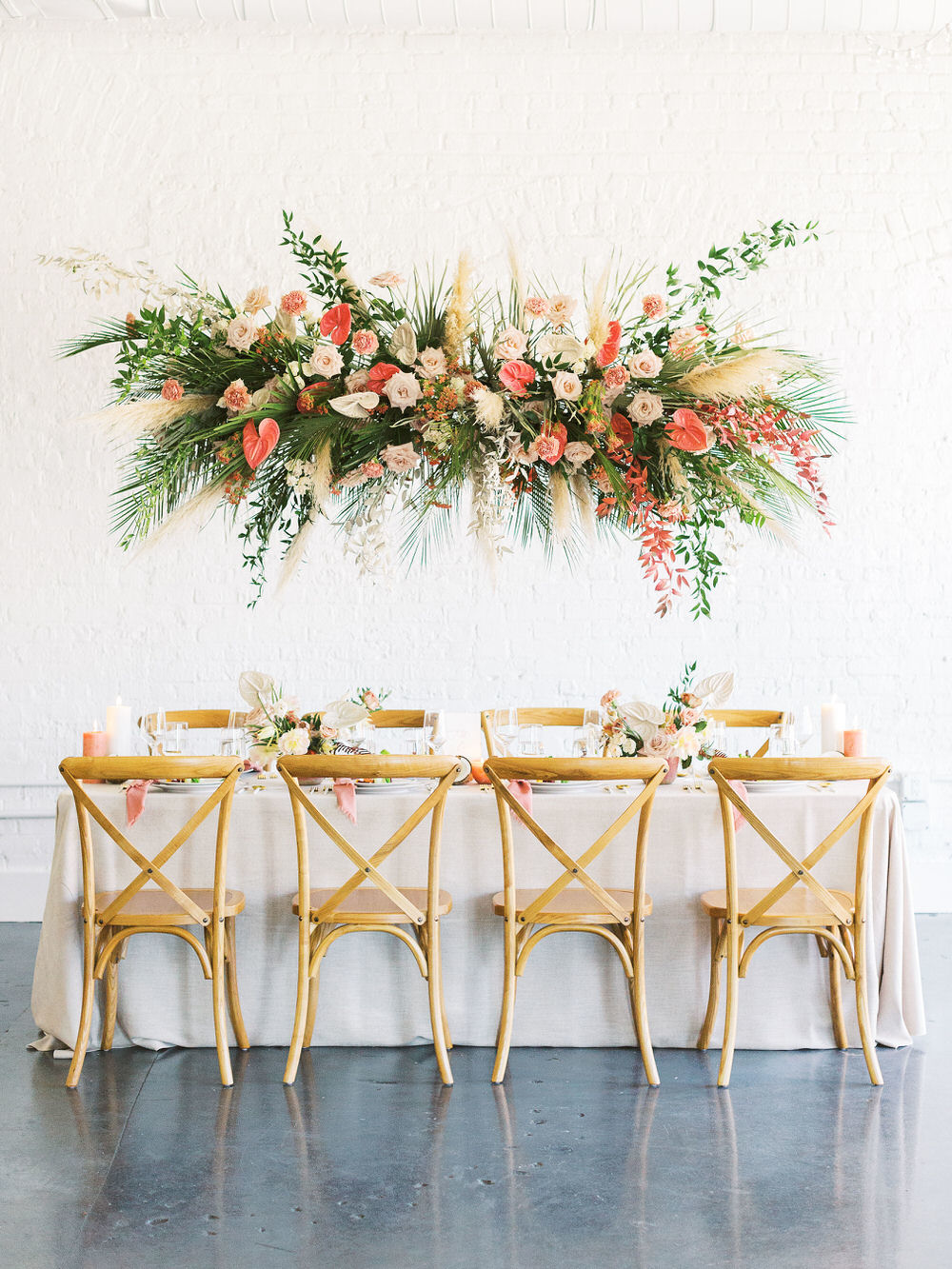 peachy wedding reception tablescape with tropical greens textured floral decor