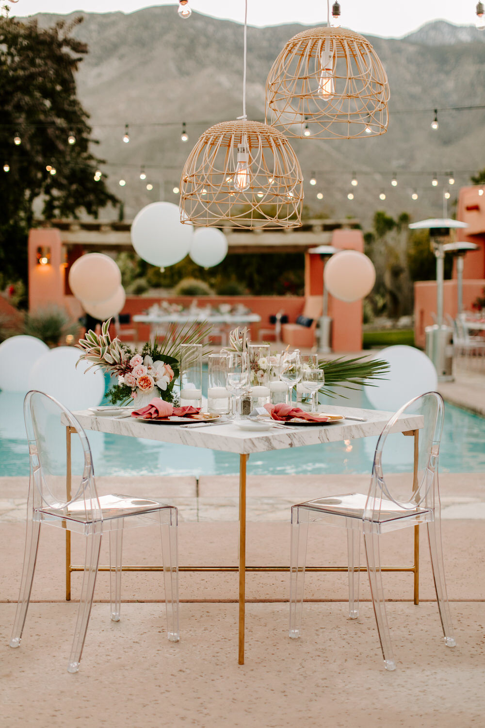 sweetheart table with ghost chairs, marble table and pink tropical accents