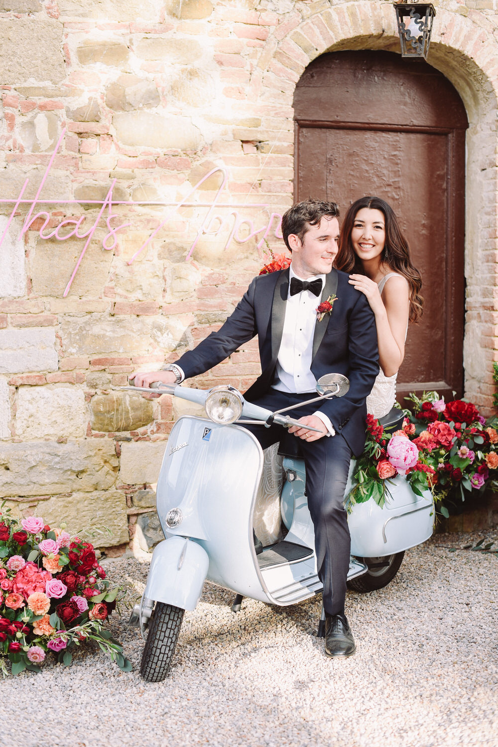 bride and groom getting ready to buzz away on their baby blue Vespa