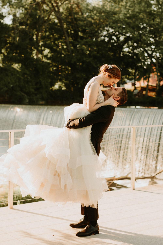 groom picks up bride to kiss