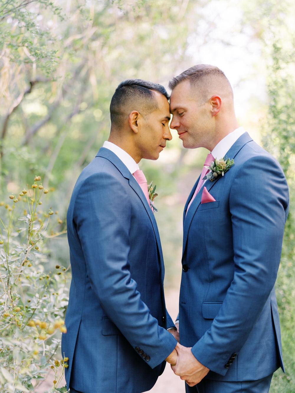 grooms touch foreheads for wedding photo