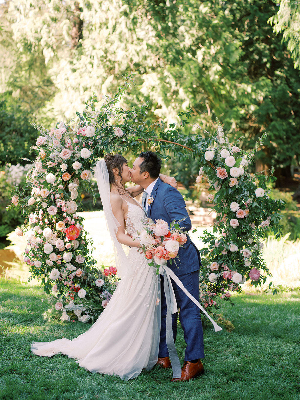 bride and groom kiss in front of floral arch