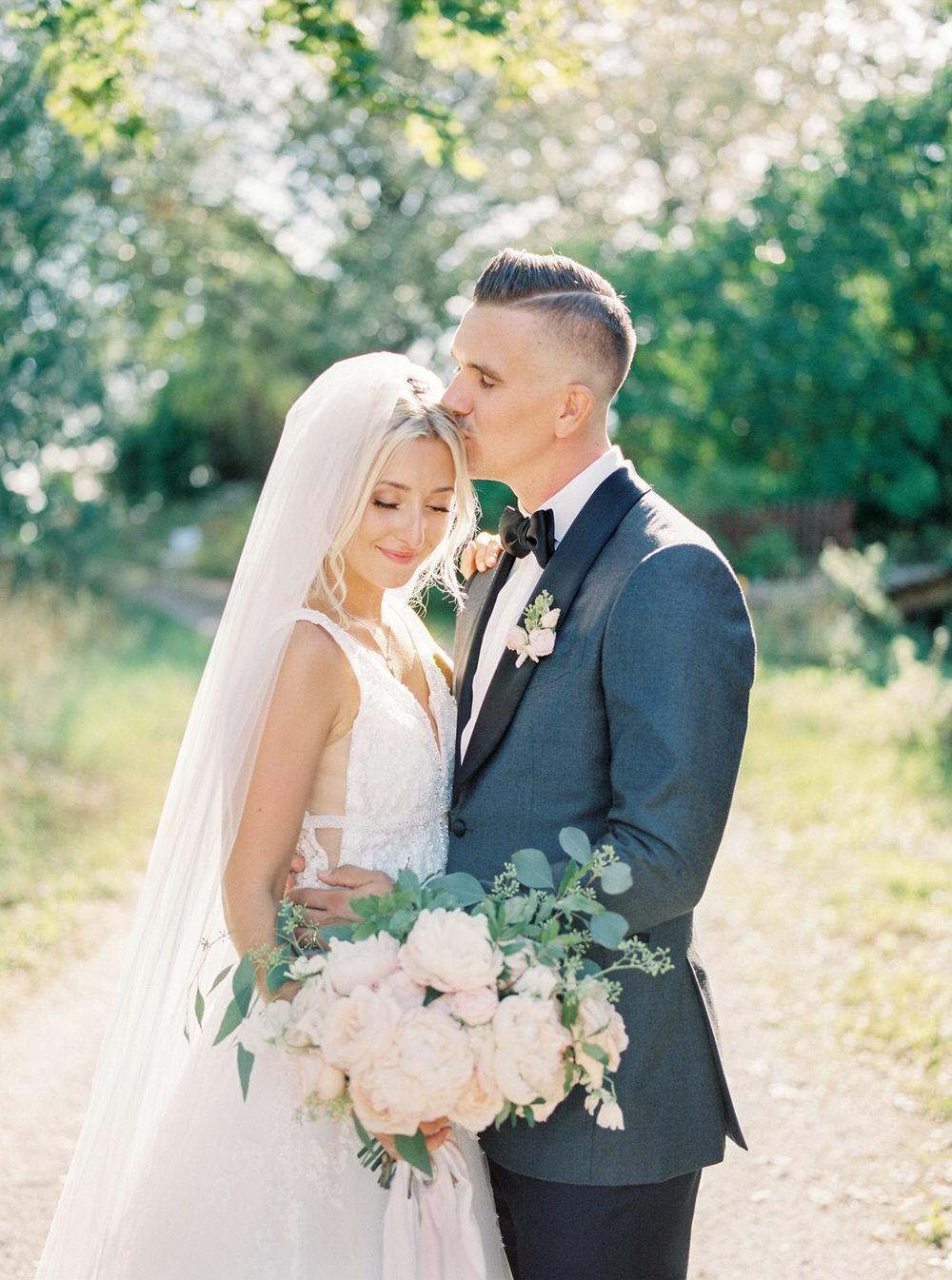 groom tenderly kisses his bride's head