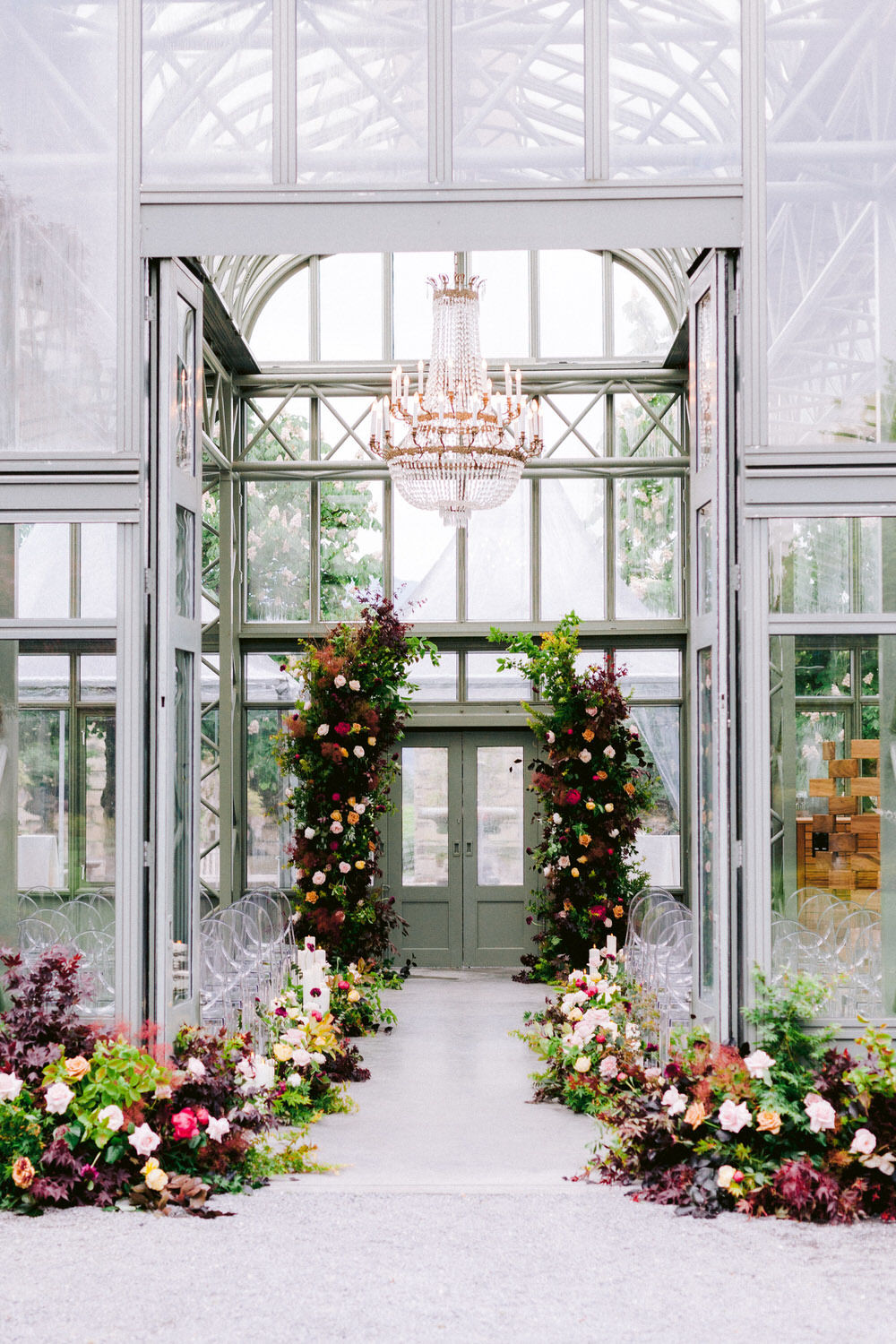 lush greenery, colorful florals, candles and ghost chairs decorate this greenhouse