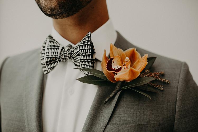 modern tropical orange boutonnieres - https://ruffledblog.com/vibrant-atlanta-wedding-inspiration-with-rust-accents