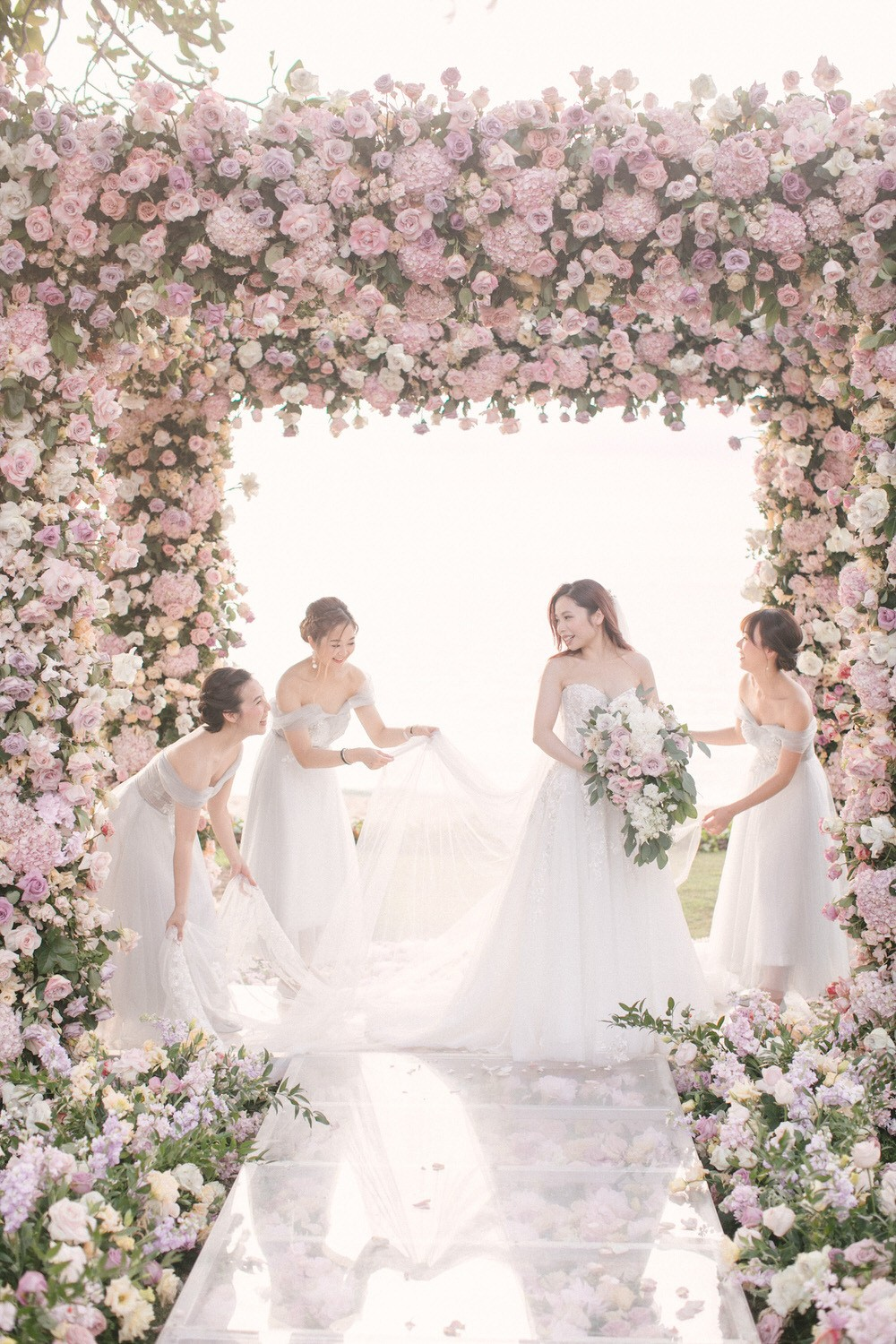bridesmaids helping the bride fix here wedding gown