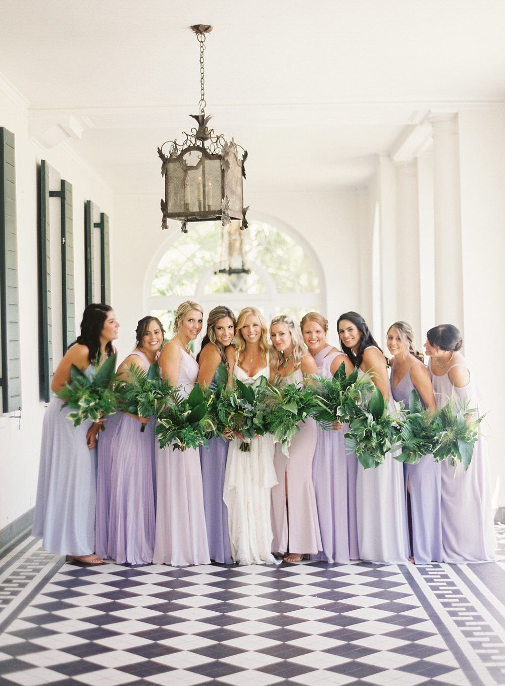 bride with her bridesmaids in an array of lavender dresses