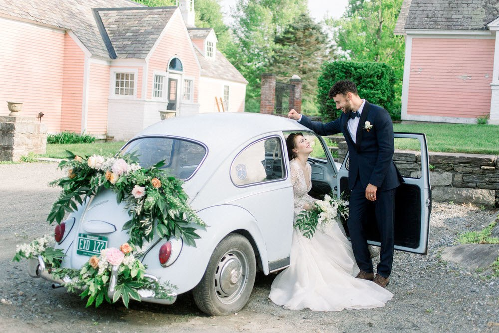 bride and groom smiling at each other as they enter the getaway car