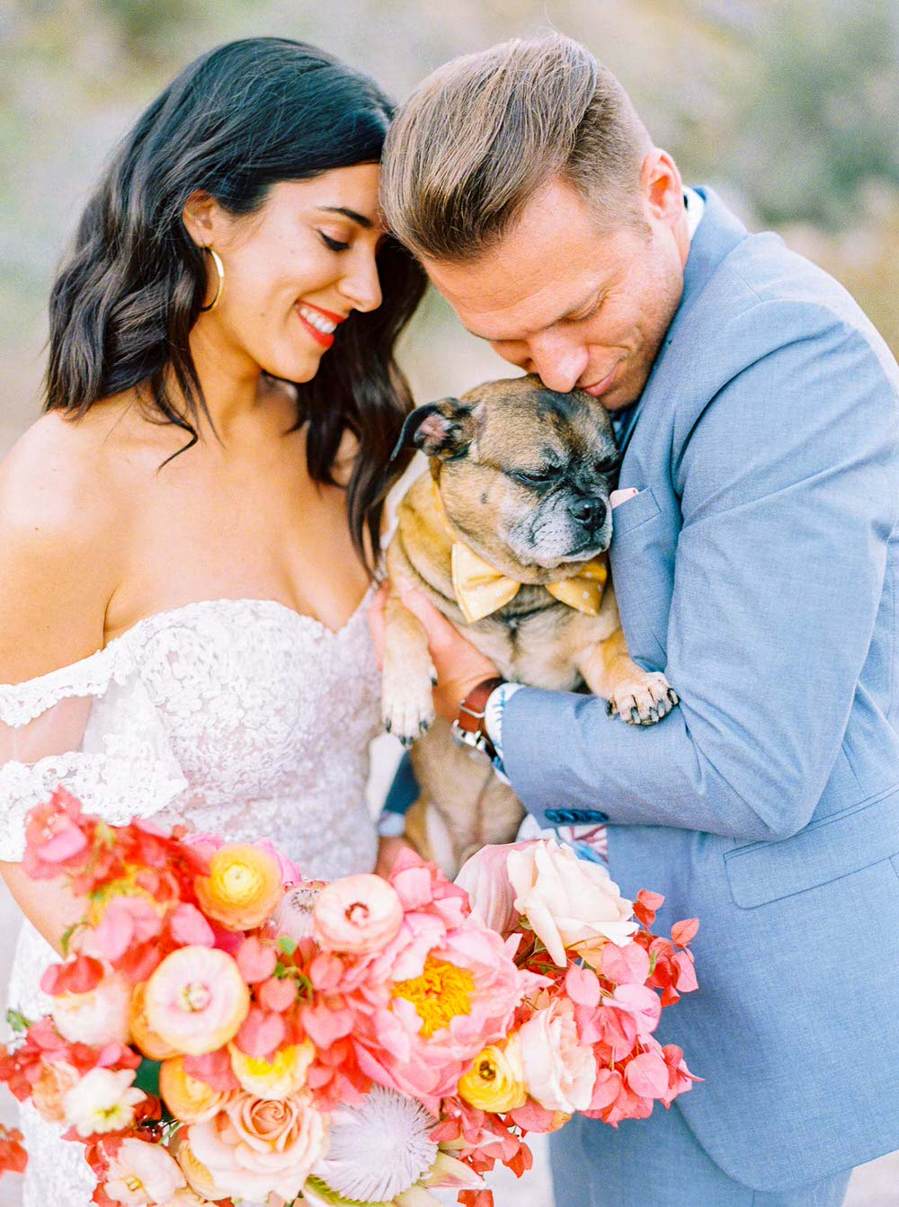 bride and groom holding their dog wearing a bowtie