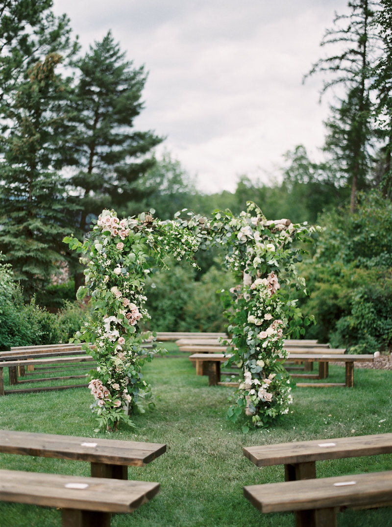 floral ceremony arch - photo by Rebecca Hollis https://ruffledblog.com/an-intimate-montana-wedding-awash-in-pink