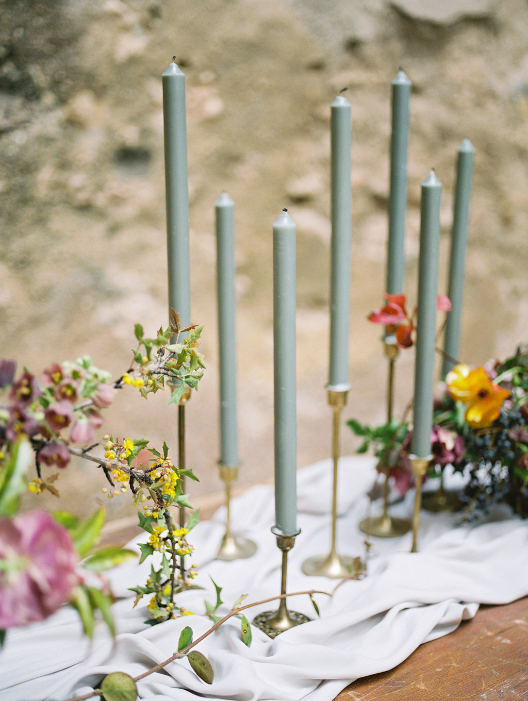 centerpieces with candlesticks - photo by Charla Storey https://ruffledblog.com/architectural-san-antonio-mission-wedding-inspiration