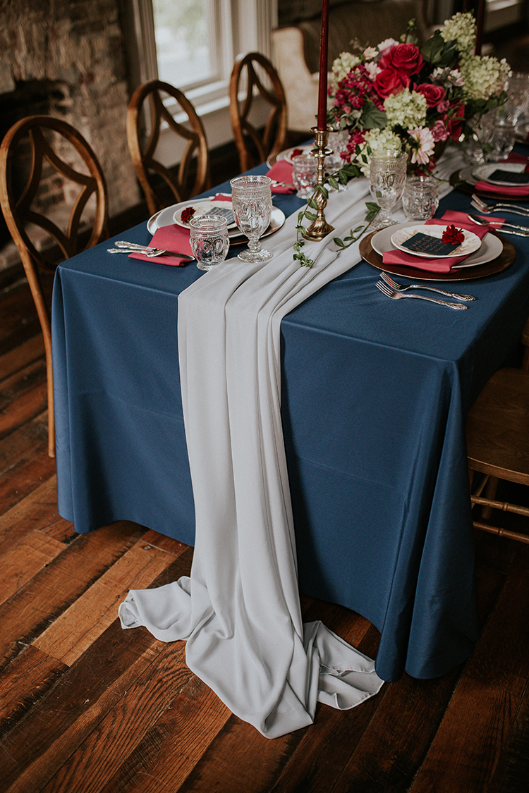 blue table runners - https://ruffledblog.com/artist-inspired-wedding-ideas-with-oxblood-and-navy