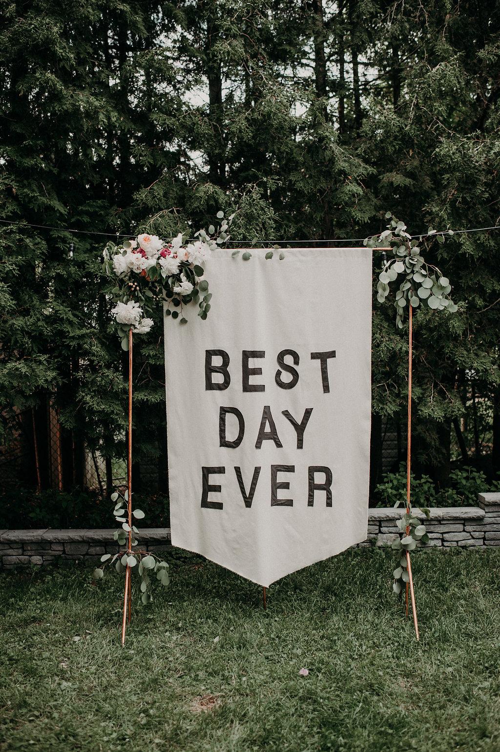 backyard wedding at home with a banner backdrop ruffled