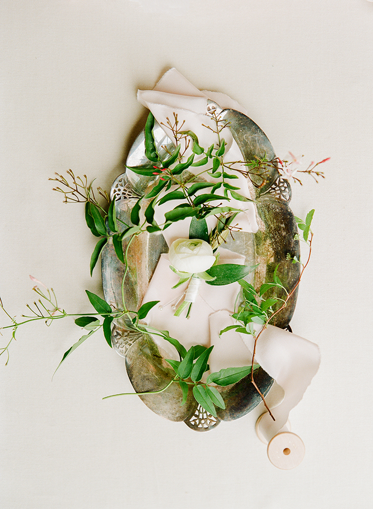 soft ivory ranunculus boutonnieres - photo by Lisa Blume Photography https://ruffledblog.com/black-tie-washington-dc-wedding-with-a-floral-wall