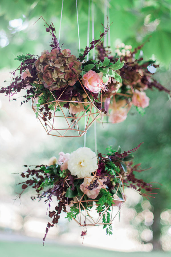 burgduny floral arrangements in geometric holders - photo by Blush and Mint Photography https://ruffledblog.com/40-eye-catching-geometric-wedding-ideas