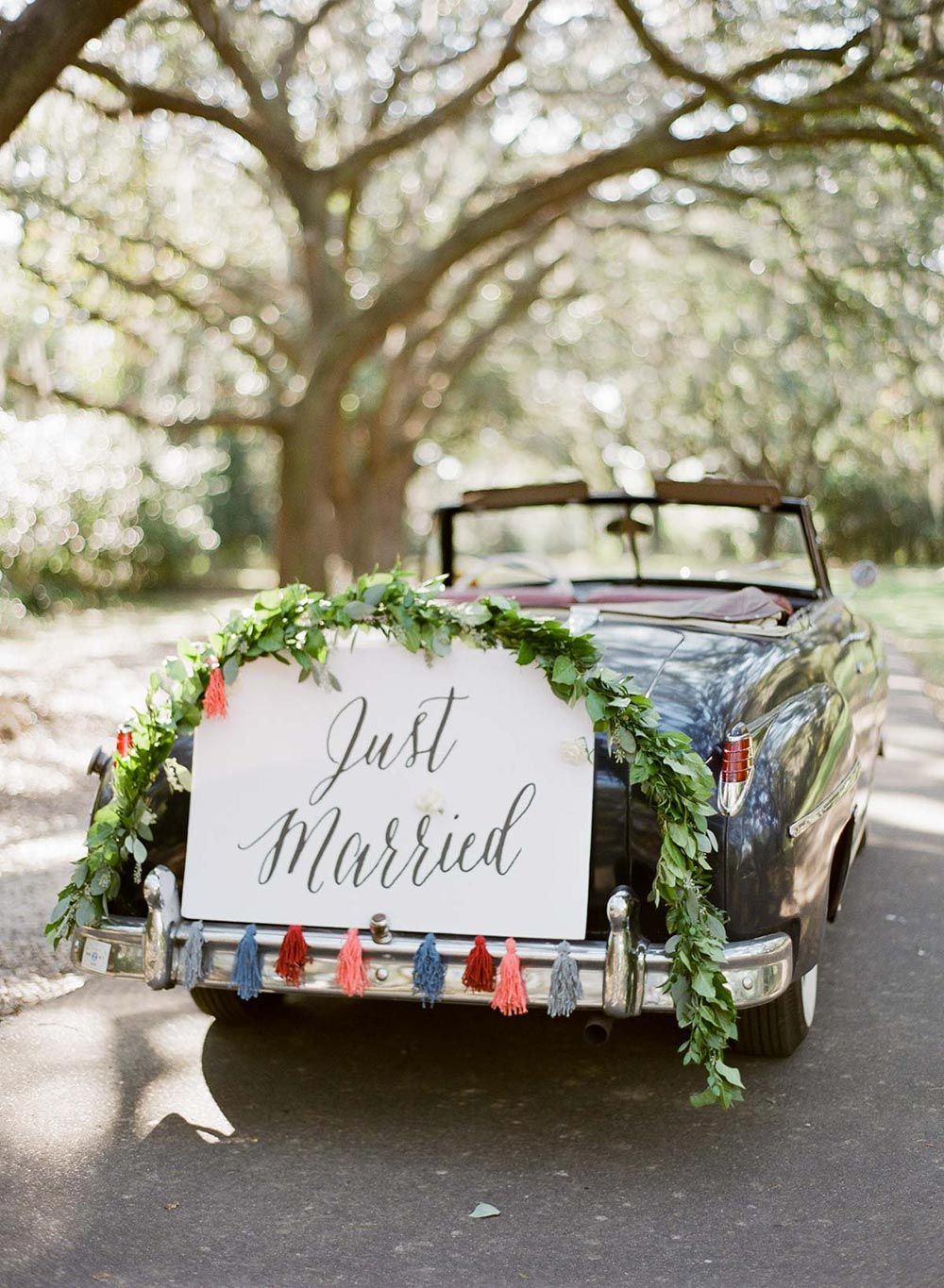 wedding getaway car with just married sign and tassel garland