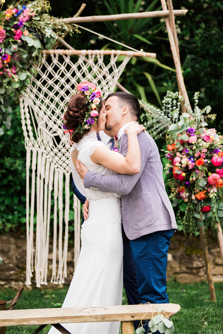 wedding ceremony kiss - photo by Passionate https://ruffledblog.com/bohemian-wedding-in-portugal-with-bright-flowers-everywhere