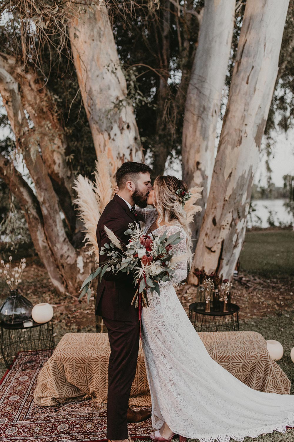 lace wedding dress and burgundy groom suit with pampas grass wedding backdrop