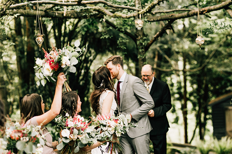 ceremony kisses - photo by Jenna Bechtholt Photography https://ruffledblog.com/boho-pacific-northwest-forest-wedding-with-king-protea