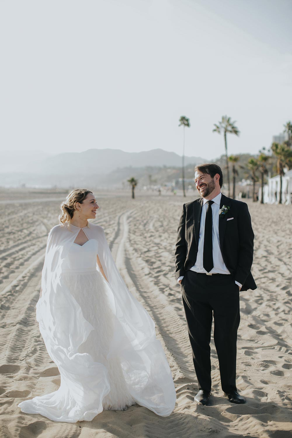 bridal cape and feathered wedding dress and black groom suit