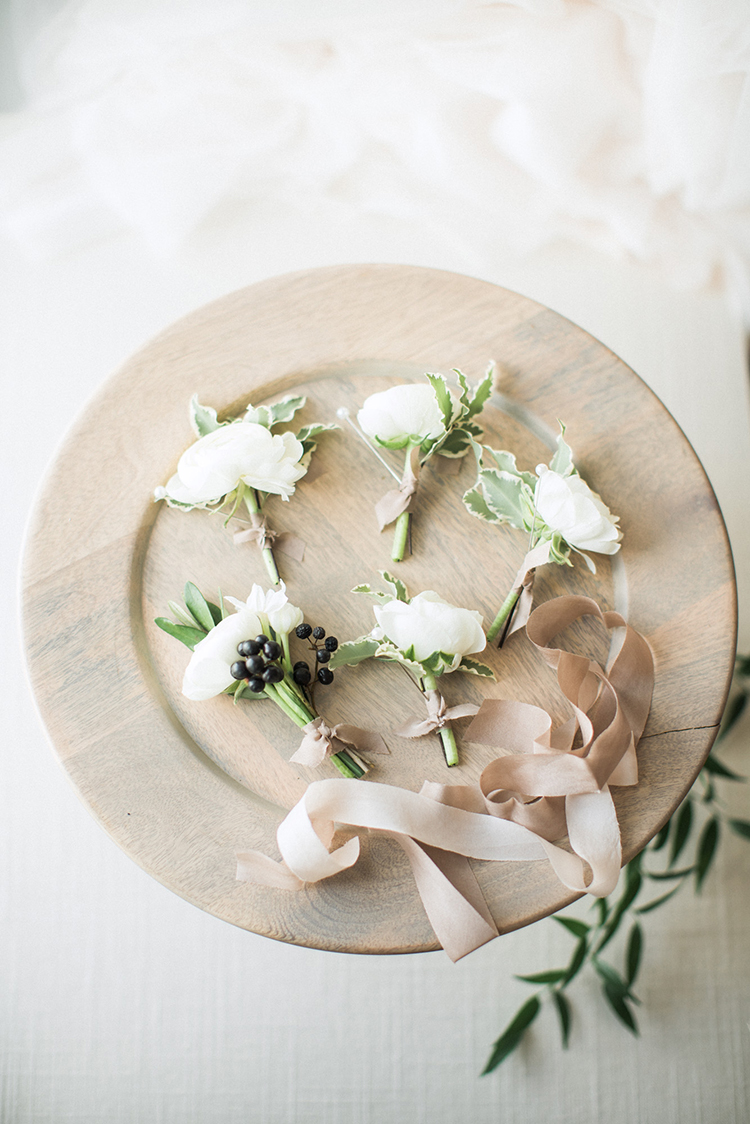 ivory wedding boutonnieres - photo by Hunter Ryan Photo http://ruffledblog.com/breezy-seaside-wedding-with-cascading-greenery