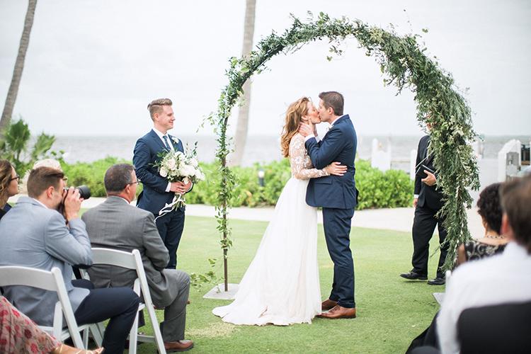 ceremony kiss - photo by Hunter Ryan Photo http://ruffledblog.com/breezy-seaside-wedding-with-cascading-greenery