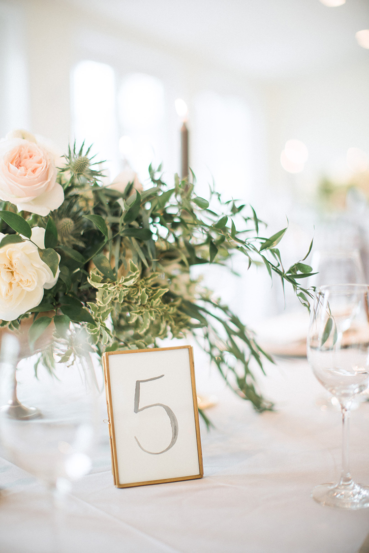gold framed table number - photo by Hunter Ryan Photo https://ruffledblog.com/breezy-seaside-wedding-with-cascading-greenery